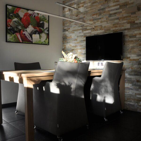 Mooie wand in de keuken met Natuurstenen Steenstrips. De Televisie komt extra mooi uit.