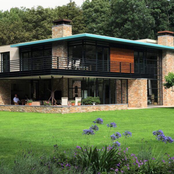 Moderne villa in het bos met natuurlijke steenpanelen.