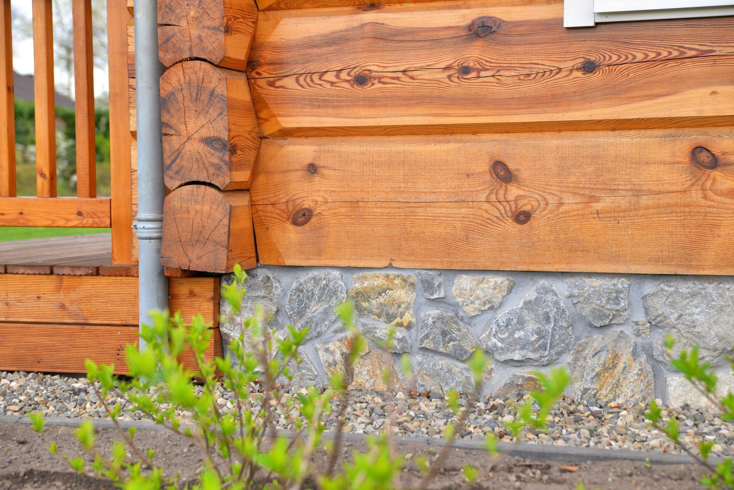 Natuursteen op de plint van houten woning.