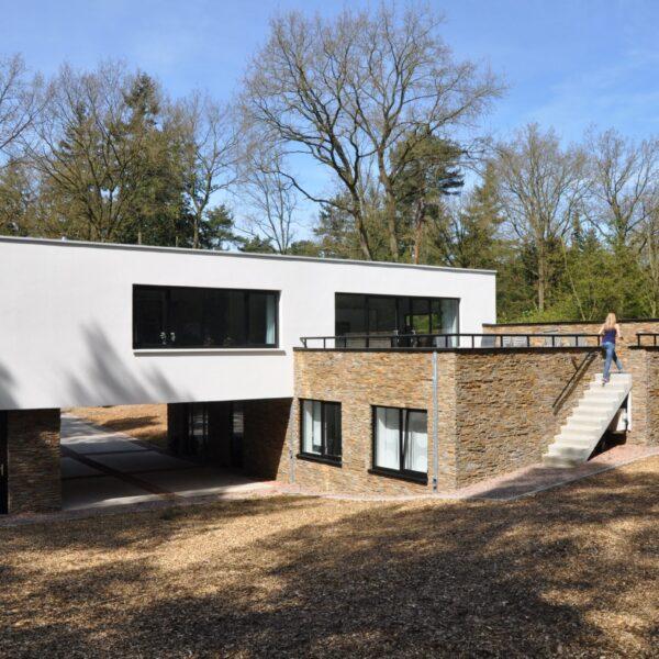 Gevelbekleding Natuursteenstrips. Moderne villa in een bosrijke omgeving.