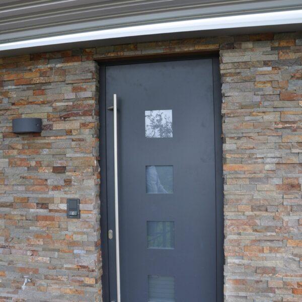 Natuursteenstrips toepgepast bij de voordeur. Goede kleurencombinatie.