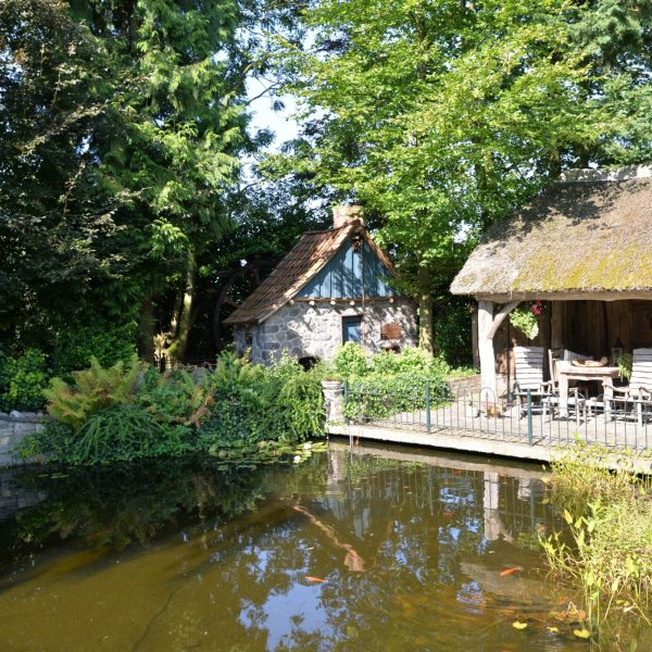 De tuin van Frans en Ell, sfeervolle veranda, bruggetje en de watermolen.