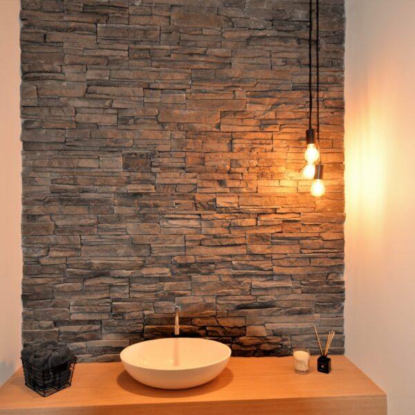 Toilet toepassing, achterwand wastafel voorzien van dezelfde steenstrips als de gevelbekleding.