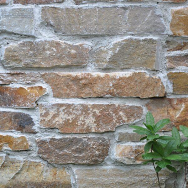 Steenstrips Rocks Oranje op de wand. Sfeervolle veranda en schuur. Stapstenen in het gras en Flagstones op het terras.