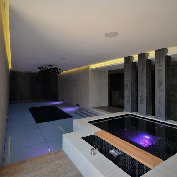 Steenstrips wand bij stijlvol binnenzwembad.